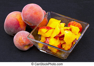 Peaches - Cut and entire peaches over a black background