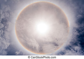 Sun with circular rainbow sun halo in sky with cloud