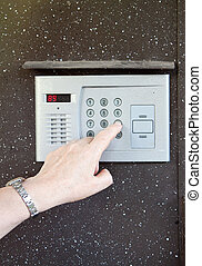 Close-up of uses intercom in steel door