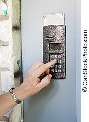 Close-up of uses intercom in steel door