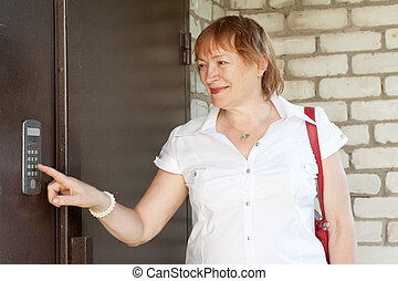 woman using house intercom - Mature woman using house...