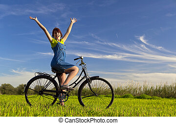 Enjoying the Spring - Happy girl over a bicycle and looking...