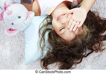Awake - Portrait of lovely girl with teddybear rubbing her...