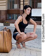 Woman waiting for a lift - Beautiful woman tourist squatting...