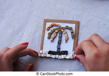 Making a stone mosaic with a natural subject and a white...