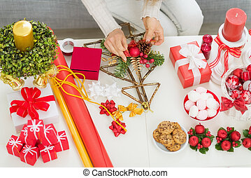 Closeup on table where woman making Christmas decorations....