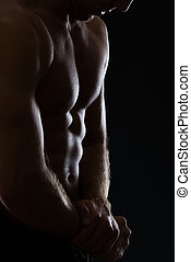 Closeup on man showing muscular body on black