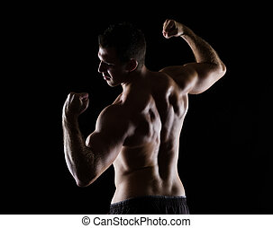 Strong sports man showing muscular back on black