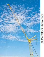 Construction crane - A yellow crane against a bright blue...