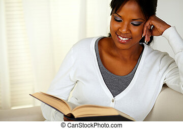 Smiling black woman reading a book - Portrait of a smiling...