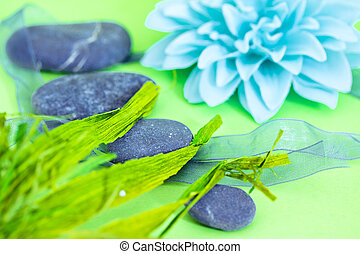 spa stones and flowers representing wellness/beauty care -...