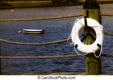 Life preserver hanging on wharf near moored boats