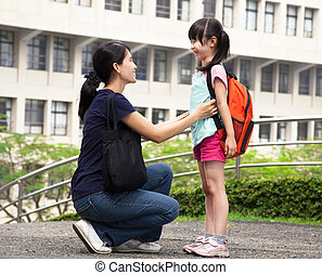 back to school.happy asian mother with daughter in school