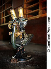 Old Microscope - Aged microscope standing on an old wooden...