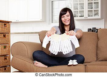 Expecting Mother with Baby Clothes - Portrait of expecting...