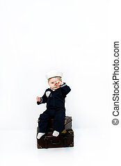 Embarcation - Little baby wearing a naval costume rubs his...
