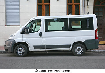 white minibus is parked in city street