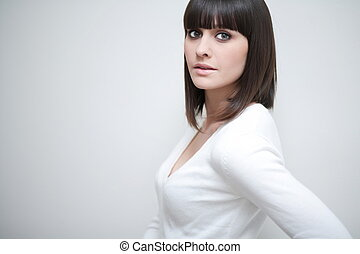 Young caucasian woman with fringe/bangs in front of a grey...