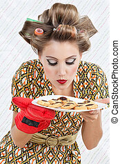 Woman Smelling Plate Of Cookies - Young woman in dress with...
