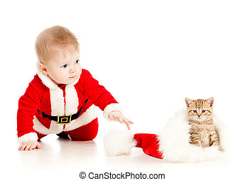 christmas baby reaching out hand for cat in a santa claus...