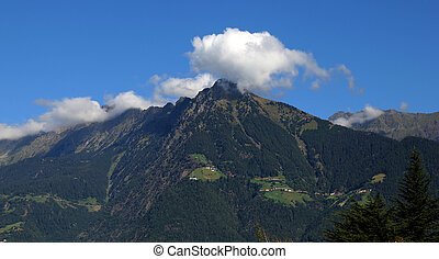 green mountains with clouds and blue sky