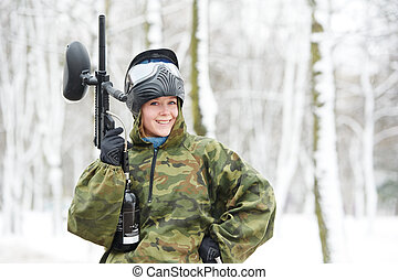 paintball player with marker at winter outdoors - happy...