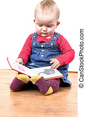 young baby girl happily reading a book - baby girl reading a...