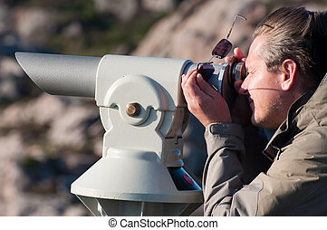 man monocular - A man looking through a coin-operated...