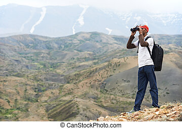 Tourist hiker with binoculars in mountains