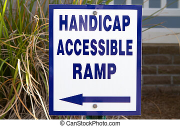 Handicap Ramp Sign - Sign in front of a building points to a...