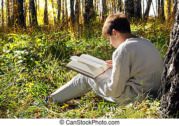 boy reading outdoor - teenage boy sit in autumn forest with...