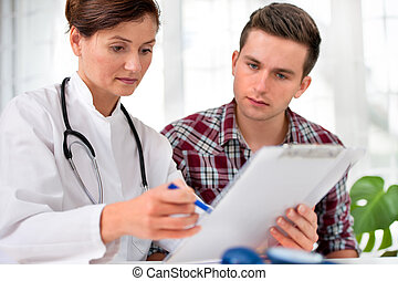 doctor with male patient - doctor talking to her male...