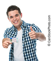 Drivers license - happy teenager showing his driving license...