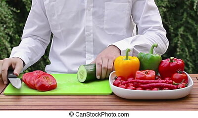 Cutting vegetable - young man cutting vegetables and tomatoe...