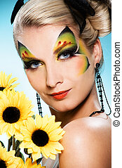 Young beauty with butterfly face-art and bouquet of...