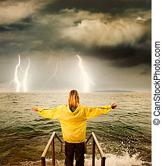 Brave woman greeting stormy ocean