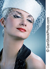 Beautiful young woman in white hat with net veil. Retro...
