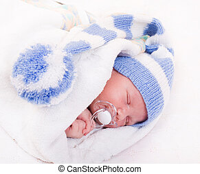 newborn baby at the age of 7 days sleeps in a knitted...