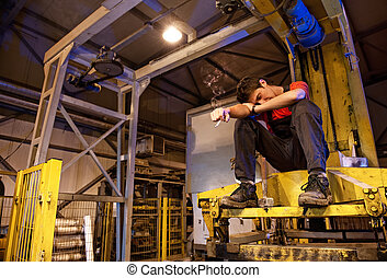 Exhaused factory worker smoking