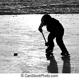 boy playing hockey on outdoor rink