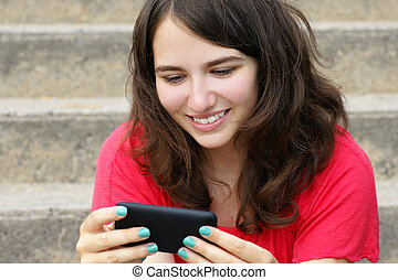 Young woman smiling at cell phone - Young woman, teenager...