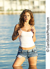 Woman in jeans shorts and a tank top