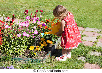 girl watering flower beds - Little girl watering flower beds