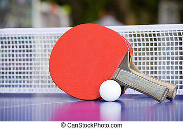 Two table tennis or ping pong rackets and balls on a blue...