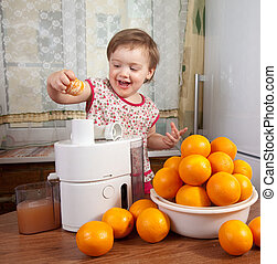 Baby girl adding orange to juicer in home kitchen
