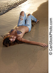 Beautiful young sexy fashion model in jeans by the sea