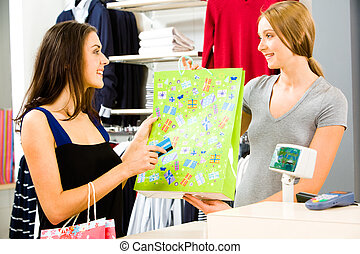 Buying clothes - Portrait of a shop assistant holding...