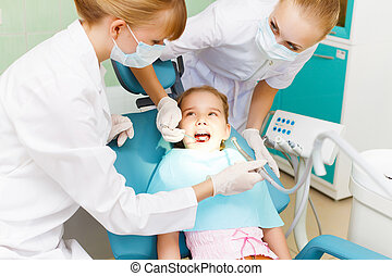 Little girl visiting dentist - Little girl sitting in the...