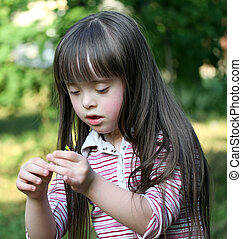 Portrait of beautiful young girl with flower in the park