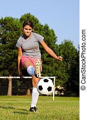 Teen girl kicking soccer ball on field
